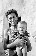Happy father holding baby boy in front of home in small desert village