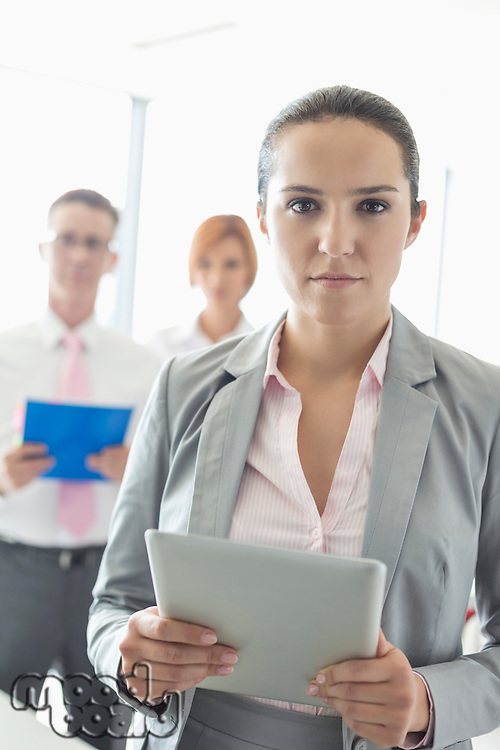 Portrait of confident businesswoman holding digital tablet with colleagues in background at office