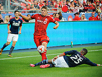 Aug 30, 2014; Toronto, Ontario, CAN; Toronto FC defender Nick Hagglund (17) avoids a sliding tackle from New England Revolution Defender Darrius Barnes (25) at BMO Field. New England won 3-0. Mandatory Credit: Peter Llewellyn-USA TODAY Sports