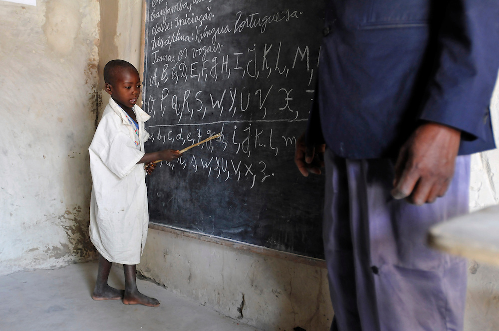 Children learning the alphabet at the Lumege-Canjamba primary school. The area around the school was contaminated with landmines during Angola's long civil war, preventing many children from coming to school and limiting the movement of those who did. Mines Advisory Group (MAG) cleared the area of mines and other remnants of war allowing children to receive an education safely and for plans to build more class rooms to accomodate an increasing number of students who are arriving under the government's Village Reunification Program - a program that encourages families living in remote hamlets to move to larger villages so that the government can provide basic services such as education, health care, water and electricity. .Lumege Canjamba, Angola. 30/09/2010.Photo © J.B. Russell