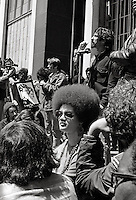 Kathleen Cleaver foreground with Tom Hayden talking at Free Huey Newton rally at Federal Building in San Francisco.  on Mayday 1969