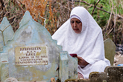June 16, 2018 - Lhokseumawe, Indonesia - A woman seen praying next to a grave during the pilgrimage..Muslims seen with their relatives' grave during a pilgrimage at the public cemetery in Lhokseumawe City. Most Muslims in Aceh already made the last grave pilgrimage before entering the holy month of Ramadan and on the day of Eid al-Fitr, to pray for the families of those who have died. (Credit Image: © Maskur Has/SOPA Images via ZUMA Wire)