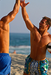 Two shirtless men on the beach celebrating a win in volleyball