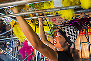 19 JANUARY 2014 - BANGKOK, THAILAND:  A member of the cast hangs part of his costume off the rigging below the stage during a mor lam show in Khlong Tan Market in Bangkok. Mor Lam is a traditional Lao form of song in Laos and Isan (northeast Thailand). It is sometimes compared to American country music, song usually revolve around unrequited love, mor lam and the complexities of rural life. Mor Lam shows are an important part of festivals and fairs in rural Thailand. Mor lam has become very popular in Isan migrant communities in Bangkok. Once performed by bands and singers, live performances are now spectacles, involving several singers, a dance troupe and comedians. The dancers (or hang khreuang) in particular often wear fancy costumes, and singers go through several costume changes in the course of a performance. Prathom Bunteung Silp is one of the best known Mor Lam troupes in Thailand with more than 250 performers and a total crew of almost 300 people. The troupe has been performing for more 55 years. It forms every August and performs through June then breaks for the rainy season.              PHOTO BY JACK KURTZ