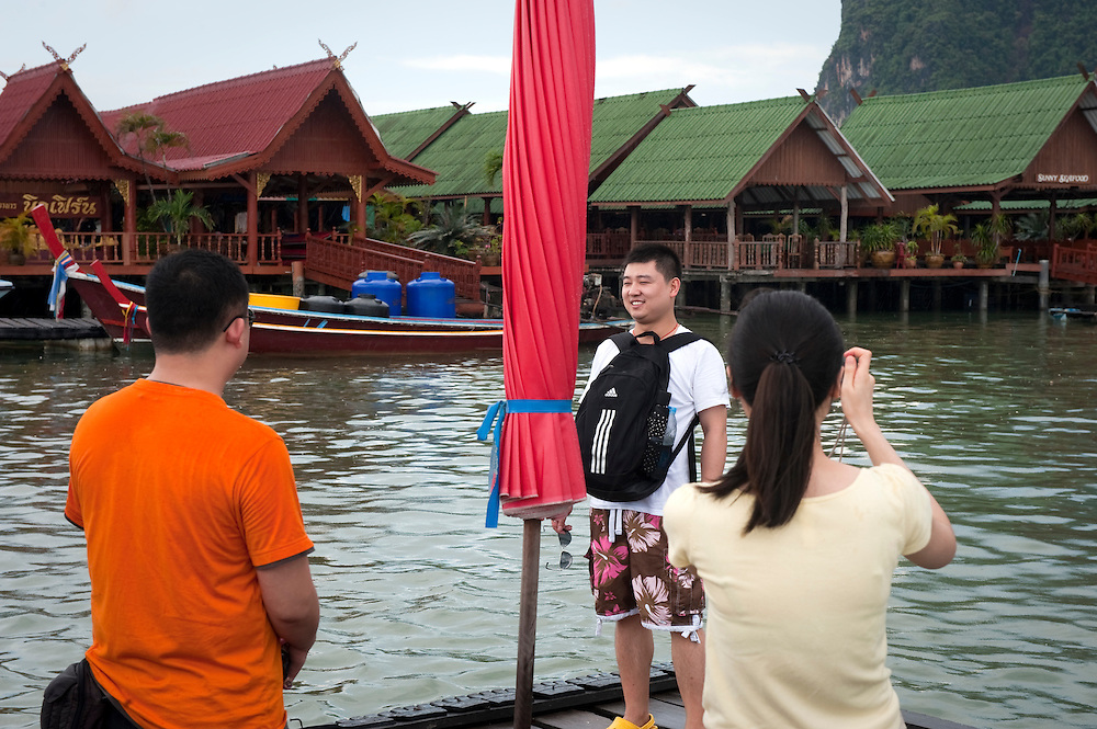 Tourists take photos of each other in the rain on one of the 'James Bond Islands', Phuket, Thailand.