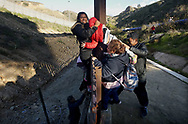 TIJUANA, MEXICO - JANUARY 06: Honduran migrants climb over the U.S.-Mexico border fence along  on January 6, 2019 in Tijuana, Mexico.  The U.S government is going into the third week of a partial shutdown with Republicans and Democrats at odds on agreeing with President Donald Trump's demands for more money to build a wall along the U.S.-Mexico border.(Photo by Sandy Huffaker/Getty Images)