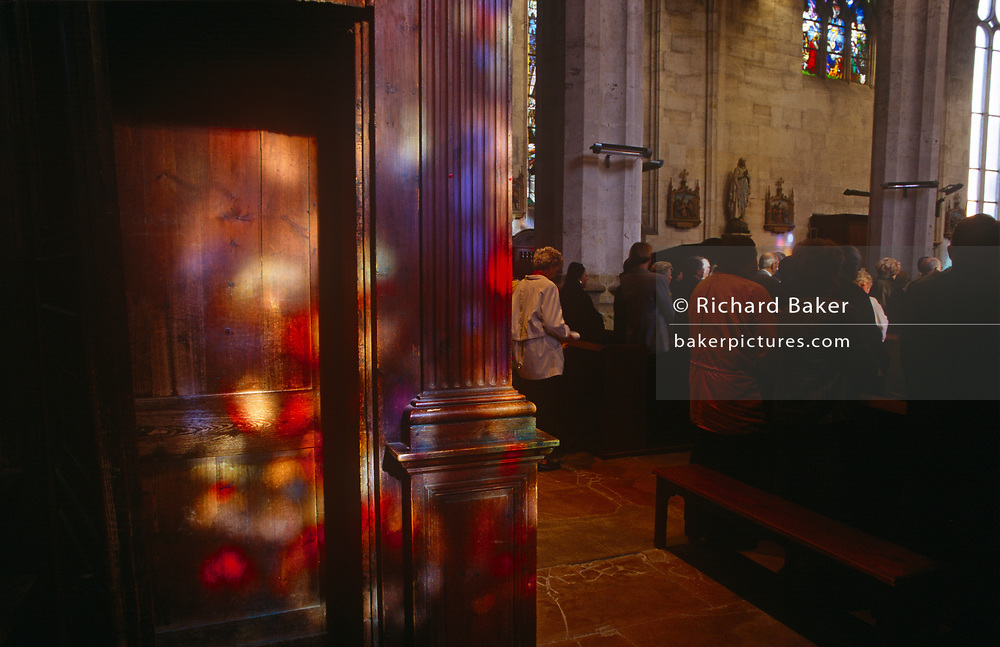Colours from stained glass windows play on a pillar during Mass held in a local rural Catholic church, on 15th October 1997, in Neubourg, Normandy, France
