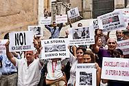 """Roma 9 Settembre 2015<br /> Manifestazione degli """"Urtisti"""" chiamati così a Roma che sono i venditori ambulanti di souvenir di papi, Madonne e rosari che protestano in Campidoglio perché  sono stati spostati dalle loro postazioni nella zona del Colosseo per decisioni dell'amministrazione comunale. Gli  """"urtisti"""" romani sono 112, tutti con regolare licenza, sono tutti ebrei meno uno cristiano. L'urtista è un mestiere che risale alla fine dell'Ottocento quando, con una concessione papale viene permesso ai soli ebrei romani, ancora chiusi nel ghetto, di vendere rosari ai pellegrini. Il nome urtisti, deriva  a quel piccolo urto, con la cassetta piena di santi, papi, madonne e rosari, portata al collo  davano ai pellegrini di piazza San Pietro per attrarre l'attenzione.<br /> Rome September 9, 2015<br /> Demostration of """"Urtisti"""" so called in Rome that are the souvenir hawkers of popes, Madonnas and rosaries against the decision of the Mayor of Rome Ignazio Marino, of remove from the Colosseum the souvenir hawkers. The """"urtisti"""" Romans are 112, all with a regular license, are all Jews but one Christian. The urtista is a craft that dates back to the nineteenth century when, with a papal concession is allowed only to the Roman Jews, still closed in the ghetto, to sell rosaries to pilgrims. The name urtisti, comes to that little bump, with the box full of saints, popes, Madonnas and rosaries, worn around the neck gave the pilgrims to St. Peter's Square to attract attention."""