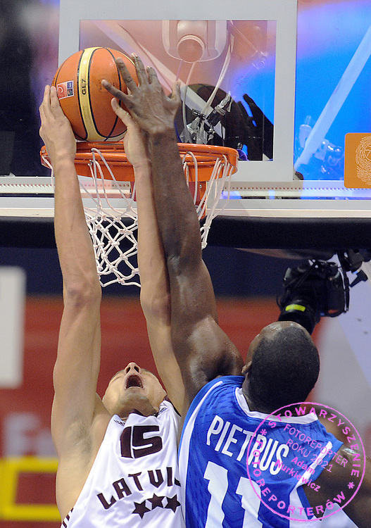 (L) Andris Biedrins of Latvia slam dunks the ball next to (R) Florent Pietrus of France during the EuroBasket 2009 Group B match between France and Latvia on September 8, 2009 in Gdansk, Poland.  ( Photo by Adam Nurkiewicz / Mediasport )
