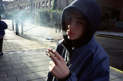 Young teenage boy wearing hooded top smoking cigarette in the street on housing estate Lambeth Walk South London c.2000