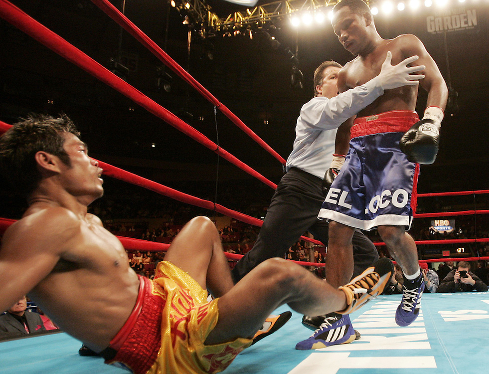 Vincente Mosquera (R) is held by a referee after knocking down Yodsanan Nanthachai (L) during their WBA superfeatherweight Championship fight at Madison Square Garden Saturday 30 April 2005. Mosquera defeated Nanthachai by unanimous decision in 12 rounds.