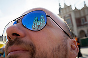 Reflections in a tourist's sunglasses of the Church of St Mary on Rynek Glowny market square, on 23rd September 2019, in Krakow, Malopolska, Poland.