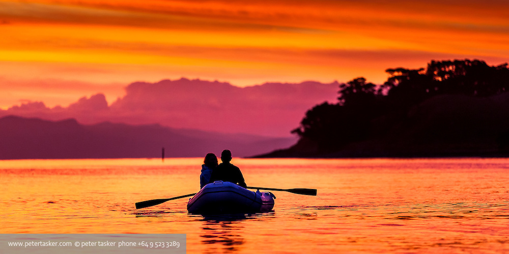 A couple observing an intense sunset while rowing their inflatable dinghy at Parapara Bay, Great Mercury Island, New Zealand.