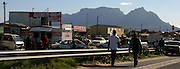 On the outskirts of Khayelitsha township people are getting busy on the road. Table Mount and Lion's Head, two icons of Cape Town, are visible in the background.