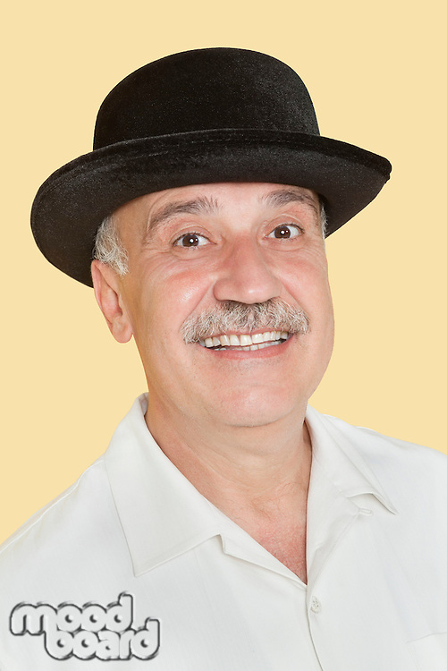 Portrait of happy senior man with black hat over yellow background