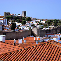 Fortified Wall Surrounding Óbidos, Portugal <br /> Óbidos is a very small town of about 3000 Portuguese along the country's western border facing the Atlantic Ocean.  Its name is from the Latin word for fortified city which is appropriate because it is surrounded by a defensive wall that was originally built by the Moors in the 8th century.