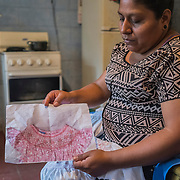 """Andre is a """"bordadora"""", a talented seamstress who works from home for the clothes factory Confetti, for which she sews manually extreme difficult clothes' decorations. Once a week she and other """"bordadoras"""" go to a small house inside her village, Las Casitas, 30 km from San Salvador, where the owner of the factory collect their work and pays them. She gets paid around 2.85 US dollars for piece. It takes her a whole day to sew one piece. She has to deliver around 10, 15 pieces per week, so she basically works no-stop all week long with lots of stress and pression as the owner takes her out 20 cents of dollar for every piece that she is not able to deliver on time. Usually, the clothes they work on, are then sold in the United States for around 200 US dollar in the upscale clothes shops of the 5th Avenue in New York"""