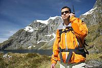 Hiker using walkie-talkie on mountain trail