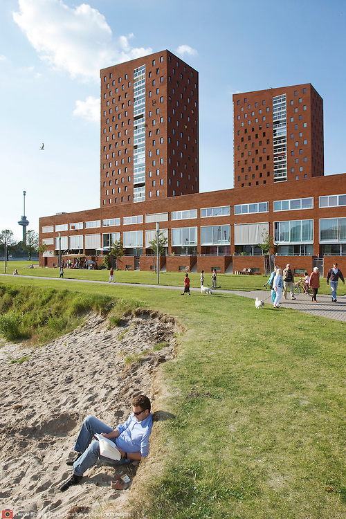 """Nederland Rotterdam 30-05-2009 20090530 Foto: David Rozing ..Nieuwbouw woningen in probleemwijk Katendrecht, man leest boek aan het strandje terwijl een kind in het zand speelt, met op de achtergrond de nieuwbouw woningen en euromast. Stedelijke vernieuwing, relaxen, relaxed, ontspanning, vrije tijd, van het zonnetje genieten, zomers, lekker weer,  zomerse dag, zomers, zonnig, zonnige, zon, genieten, ontspanning, rust, huisje boompje beestje, ruime moderne wijk, vrij uitzicht, strand New houses / appartments in (former) deprived area / projects """"Katendrecht """" This area is on a list with projects which need help of the government because of degradation in the area etc.city, beach, project, suburb, suburbian, problem. Neighboorhood, neighboorhoods, district, city, problems,  daily life Holland, The Netherlands, dutch, Pays Bas, Europe ..Foto: David Rozing"""