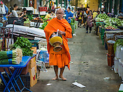"21 DECEMBER 2015 - BANGKOK, THAILAND: A Buddhist monk walks through Pak Khlong Talat, also called the Flower Market. The market has been a Bangkok landmark for more than 50 years and is the largest wholesale flower market in Bangkok. A recent renovation resulted in many stalls being closed to make room for chain restaurants to attract tourists. Now Bangkok city officials are threatening to evict sidewalk vendors who line the outside of the market. Evicting the sidewalk vendors is a part of a citywide effort to ""clean up"" Bangkok.       PHOTO BY JACK KURTZ"