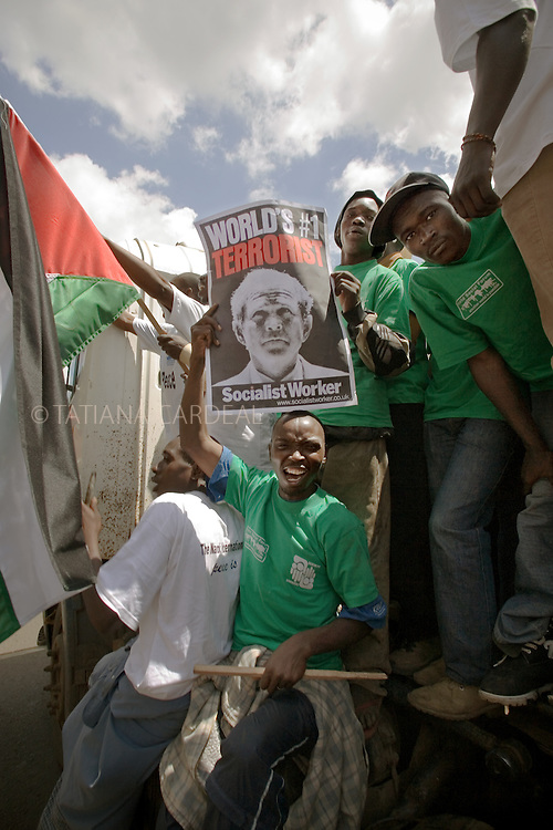 At the opening march of the 2007 World Social Forum, an anti-globalization campaigner holds up a poster depicting US President George Bush as a terrorist.Nairobi, Kenya, Africa.