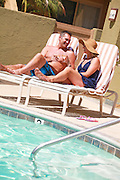 Attractive Couple Sitting on the Lounge Chairs at the Pool with Cocktails