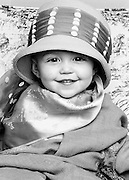 Portrait of little girl with woman's hat and scarf. One year old.