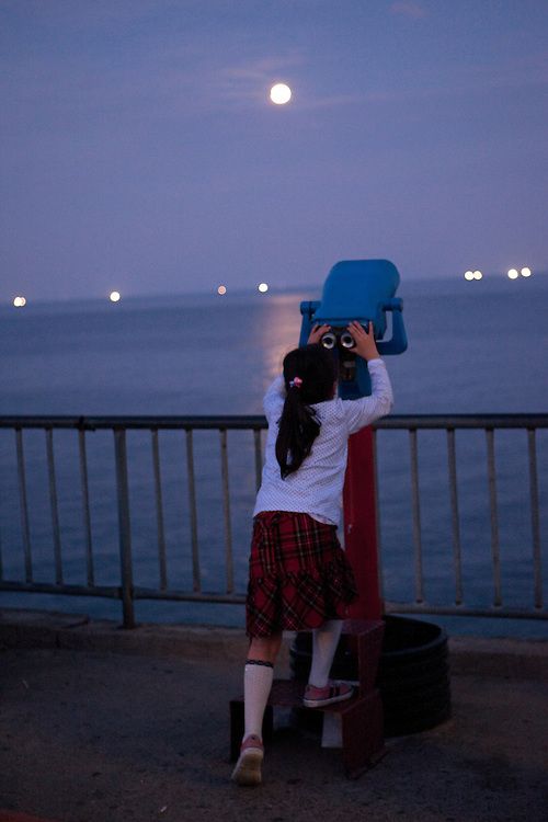 Korean girl looking through binoculars to the sea and full moon / Mangyang rest area, South Korea, Republic of Korea, KOR, 04 October 2009.