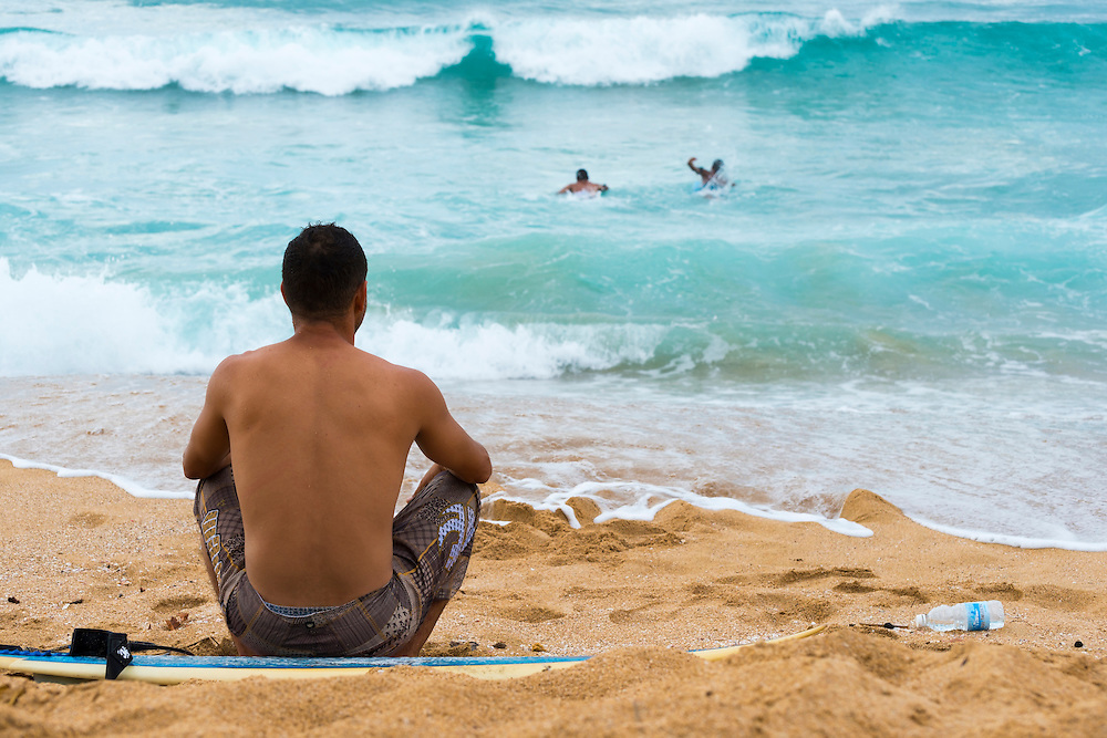 A surfer sits with his board at a beach in Arecibo, Puerto Rico (September 13, 2012)