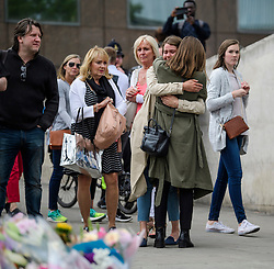 © Licensed to London News Pictures. 05/06/2017. London, UK. Emotional members of the public watch over flowers left at London Bridge, in memory of those who lost their lives in the London Bridge terror attack. Three men attacked members of the public  after a white van rammed pedestrians on London Bridge. Ten people including the three suspected attackers were killed and 48 injured in the attack. Photo credit: Ben Cawthra/LNP