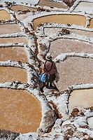 Maras, Peru - July 23, 2013: woman at Maras salt mines in the peruvian Andes at Cuzco Peru on july 23, 2013