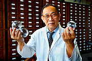 Portrait of Doctor Jian Zhong Xue holding glass cups used in Chinese medicine to help circulation.  The cups are warmed and placed open side down on specific areas of the body.  Doctor Xue is a specialist in acupuncture and Chinese herbal medicine.