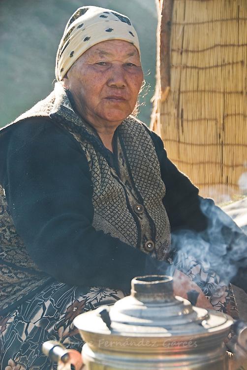 Woman doing domestic tasks outside her yurt near Karakol, Kyrgyzstan.