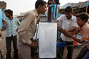 An ice-seller fastens a massive load to back of his clients utility cycle.