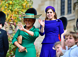 Princess Beatrice and her mother Sarah Ferguson wave to Princess Eugenie and her new husband Jack Brooksbank as they leave St George's Chapel in Windsor Castle following their wedding.