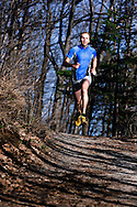 Healthy young man cross-country running in a mountain trail.