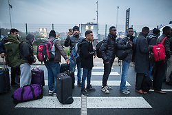 © Licensed to London News Pictures . 24/10/2016 . Calais , France . Thousands of migrants queue as they are evacuated from the Jungle migrant camp in Calais , Northern France , on the day of a planned eviction and start of the destruction of the camp . Photo credit: Joel Goodman/LNP