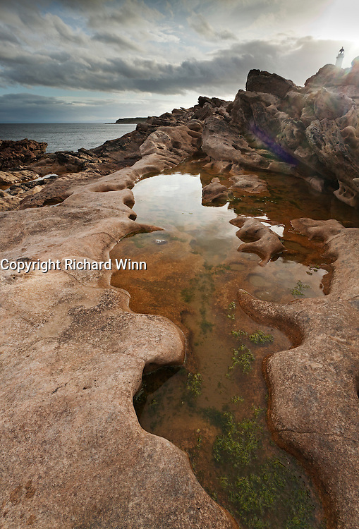 Extreme wideangle view of a distinctively-shaped rockpool at Tarbat Ness, with the lighthouse in the background.