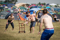 Image ©Licensed to i-Images Picture Agency. 18/07/2014  Henham Park , Suffolk, United Kingdom. Festival goers play cricket by the camp using a wheelie trolley as a makeshift set of stumps at Henham Park on what is forecast to be the hottest day of the year so far with temperatures due to hit 30 degrees centigrade. The Latitude Festival of music and arts. Picture by Joel Goodman / i-Images