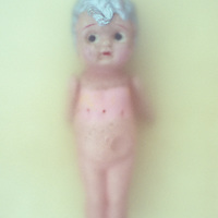 Soiled and punctured vintage celluloid naked girl doll with silver painted hair and worried expression lying on scuffed leather behind frosted glass