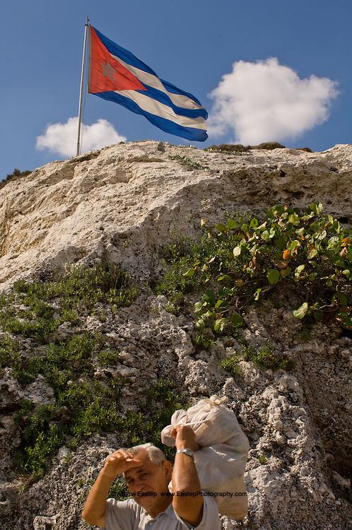 The Cuban flag flies above a rock fountain near the National Hotel. Havana, Cuba