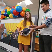 Lawndale Elementary School student Morgan Tidwell, left, receives her gifts from Google employee Brett Kelleher after winning the Google Doodle contest for the state of Mississippi.