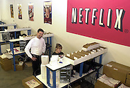 Reed Hastings, left, CEO and Co-founder of Netflix, speaks with employee Melina Guyer, at the new Phoenixville, Pennsylvania distribution center, Wednesday, February 12, 2003, in Phoenixville, Pennsylvania. Netflix plans to open one to two facilities per month for the remainder of 2003 as part of its ongoing strategy to provide one-day movie delivery to its members. By year-end 2003, Netflix expects that it will be able to reach more than 70 percent of its subscribers with generally next-day service. (Photo by William Thomas Cain)