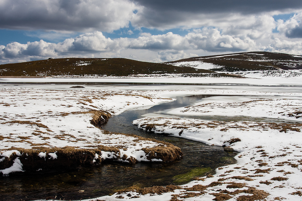 A small stream leads into the frozen Laguna de Los Peces, in the Sanabria region of Northern Spain