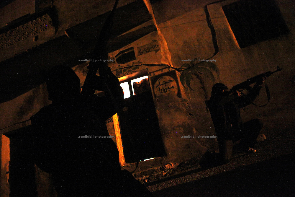 Fighters of the Free Syrian Army pointing at a sniper nest of the syrian Army in the dead of night in Al Janoudiyah, Province of Idlib, Syria. The Guerillas try to protect the villagers from the constant sniper attacks by Assads forces.