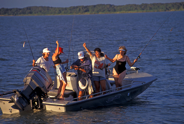 Stock photo of a group of women celebrating the catching of a fish as the guide brings it in the boat with a net