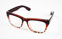 Close-up of reading glasses over white background