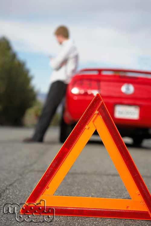Warning triangle standing by man leaning on broken down car
