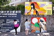 Gatuscen. En bild på en mur av en traditionellt klädd kvinna och två modernt klädda kvinnor på en trottoar vid Kyoto University, Japan