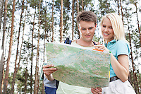 Young hiking couple reading map in forest